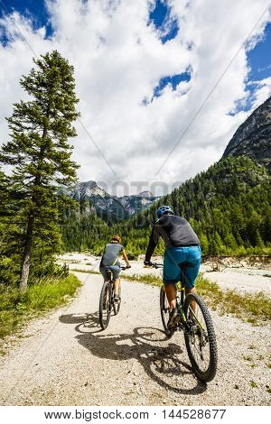 Couple on mountain bikes in the Italian Dolomites.