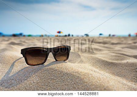 Sun glasses lie on a beach near the sea.