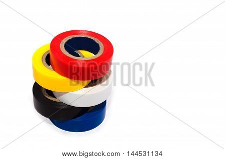 Multicolored insulating tapes roll on white background with soft shadows.