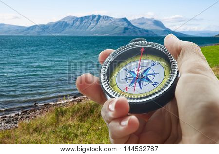 a compass and a hand in mountains