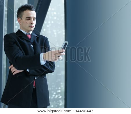 Businessman over modern winter office background (composition has some place for text over grey background)