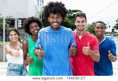 Group of international young adults showing thumbs in city in the summer