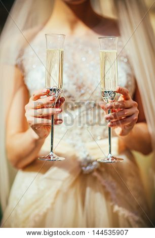Bride hold two glass with champagne in hand. Close up photo