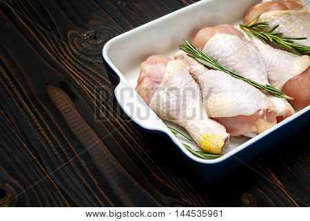 Raw chicken legs in baking dish isolated on a wooden background