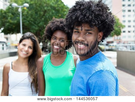 African american young adult with two beautiful girls in the city in the summer