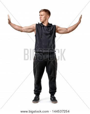 Muscled young man stands pushing invisible walls with his hands isolated on white background. Boundaries and obstacles. Solving problems. Strength and persistence.