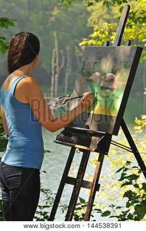 portrait of young artistic woman painting on a canvas outside in nature