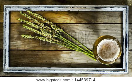 Glass of cold beer with spikelets of wheat in the old frame. On a wooden background