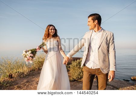 Happy just married young wedding couple celebrating and have fun at beautiful beach sunset