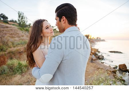 Romantic married couple kissing and hugging on the beach at sunset