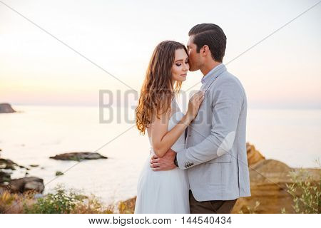 Romantic married couple kissing on the beach at sunset