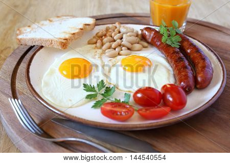 English breakfast with sausage fried eggs baked beans and orange juice
