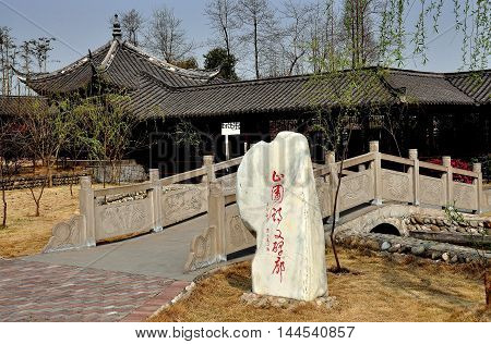 Sheng Pin China - March 7 2013: Stone with Chinese characters and small footbridge in the gardens at the General Yin Chang Heng Historic House Museum