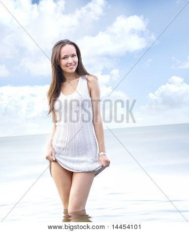 Picture of young sexy woman standing in the water (sky and ocean background)