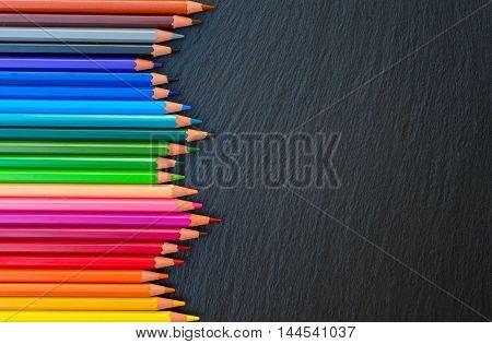 Back to school pencils color rainbow border on black board background