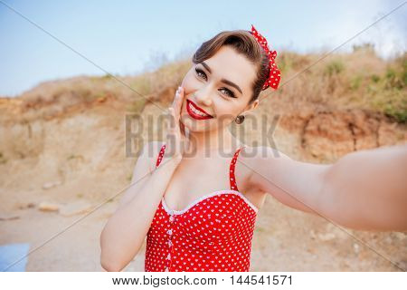 Smiling young cheerful pin up girl making selfie while standing at the beach