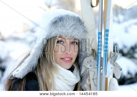 Attractive woman with ski over winter background
