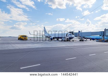 Passenger plane in the airport summer sunny day. Aircraft maintenance.