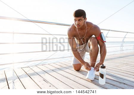 Serious african american young sportsman laces his sneakers standing on his knee at wooden terrace