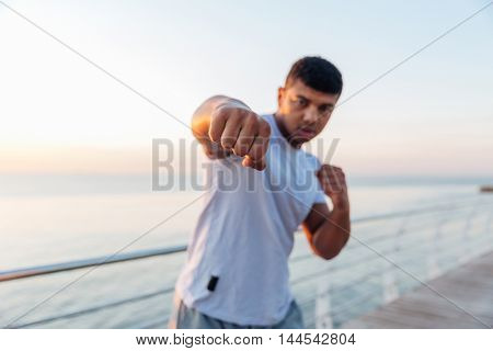 Athletic african american young man boxer standing and doing boxing training on pier