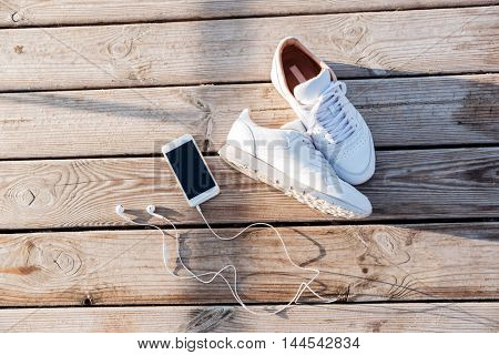 Sport concept - pair of white sneakers, smartphone and earphones over wooden background