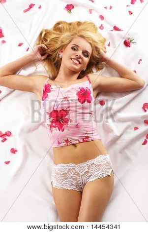 Erotic shoot of young sexy lady laying on the silk