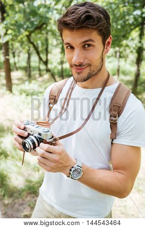 Handsome young man with backpack taking photos with old photo camera in forest