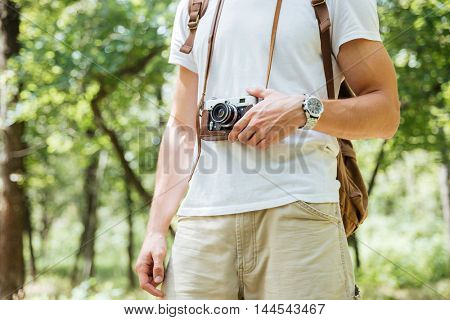 Closeup of young man with backpack and vintage photo camera in forest