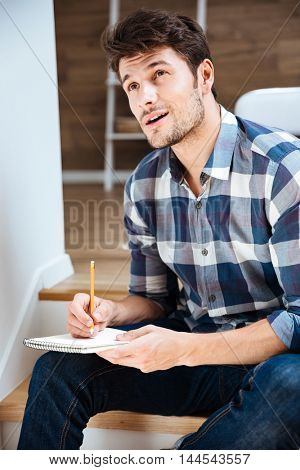 Thoughtful young man in plaid shirt thinking and writing in notepad at home