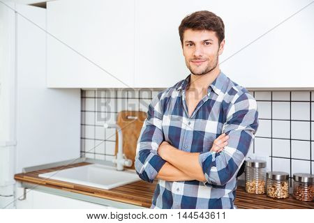 Confident young man in plaid shirt standing with arms crossed on the kitchen