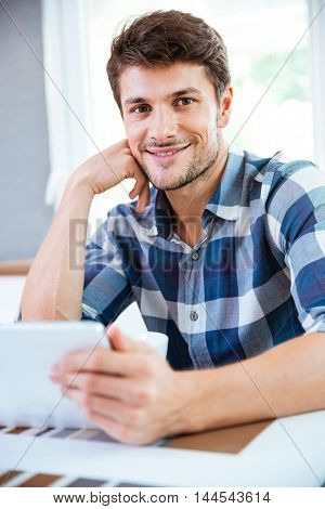 Cheerful young man in checkered shirt using tablet at the table