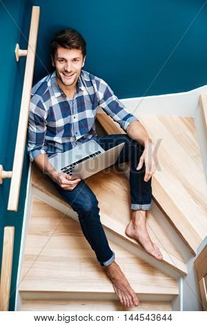 Top view of cheerful young man in checkered shirt sitting on stairs at home and using laptop