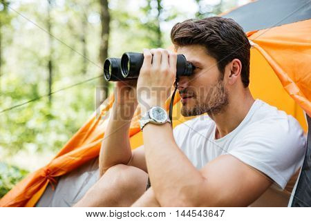 Handsome young man tourist sitting near touristic tent and looking at binoculars in forest