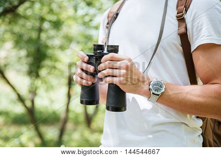 Closeup of young man with backpack and binoculars in forest