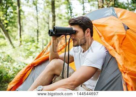 Attractive young man tourist with binoculars sitting near touristic tent in forest