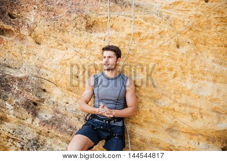 Young handsome sportsman getting ready to climb a rock cliff
