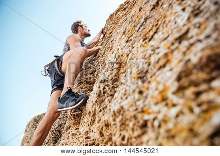 Young handsome sportsman climbing up a rock cliff