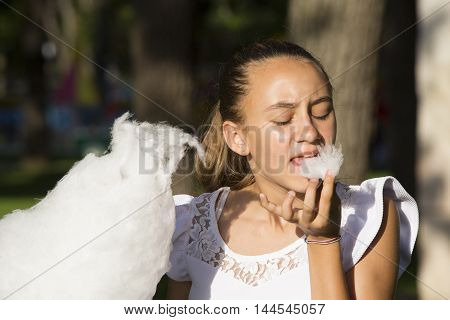 Girl eating cotton candy in a summer park