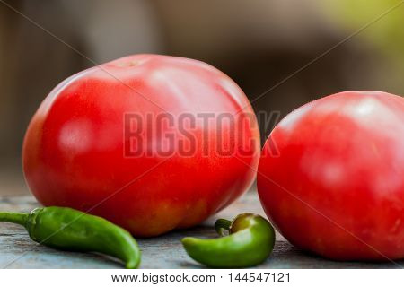 Home-grown organic ripe tomatoes and hot chili peppers on old wooden table in the village