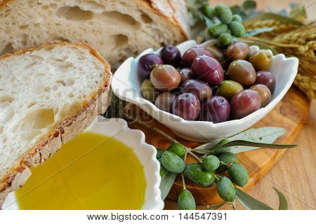 Traditional italian appetizer - fresh homemade bread extra virgin olive oil and olives on wooden background