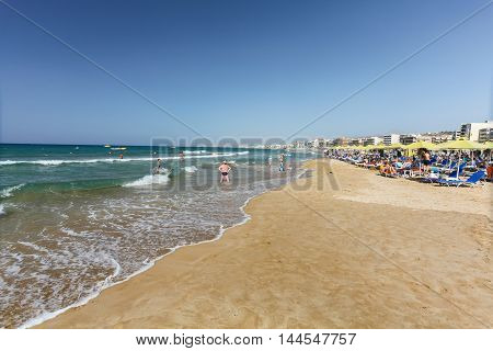 City beach with people and waves of Mediterranean Sea