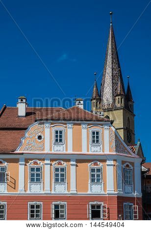 Apartment house and steeple of Saint Mary Lutheran Cathedral in Sibiu city in Romania