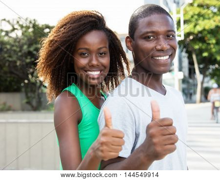 Beautiful african american couple showing thumb in the city in the summer