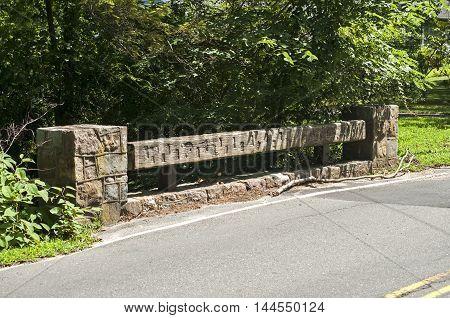Wooden railing of small bridge over river and asphalt road