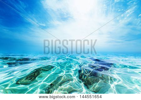Blue Water Background underwater. Sand beach on tropical island. View from sea water close up