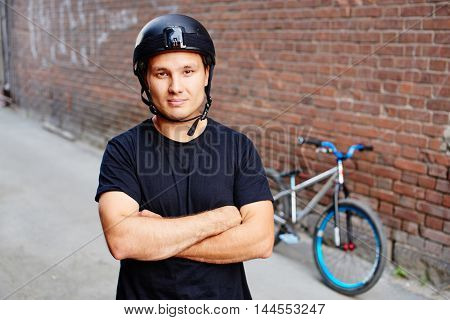 Portrait of guy rider standing next to bike in the alley of the red brick building
