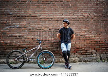 Guy cyclist in a helmet standing next to the bike at a wall from red brick