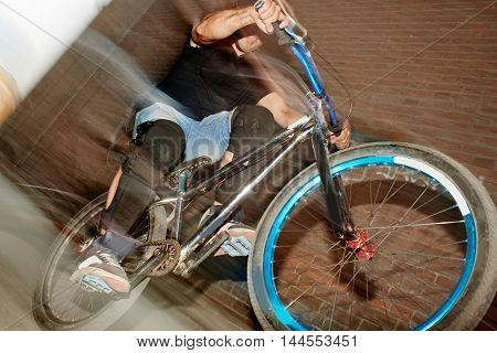 The guy's a cyclist in motion, riding on the rear wheel of the bike near the wall of the red brick building