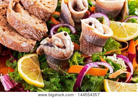 Traditional snacks salted herring with vegetables, onion, lemon, yellow lime and bread.