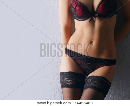 Young sexy woman in erotic lingerie over dark background